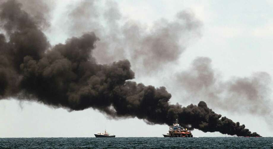Vessels monitor a oil burn in the area of the Deepwater Horizon disaster on the Gulf of Mexico, Tuesday, July 13, 2010. BP officials have placed a containment cap over the leak in hopes that the flow of oil will be diminished. (AP Photo/Dave Martin) Photo: Dave Martin, AP