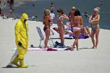 DAUPHIN ISLAND, AL.   JULY 4, 2010 :  A cleanup worker, wearing a protective coverall and carrying a small scoop, punctuates an otherwise typical holiday beach scene as  patrols the beach looking for tar balls on Independence Day.  While exact numbers are elusive, tourist business along the Gulf Coast all reported feeling the sting of lost income from a noticeable dip in tourism this summer following the Deepwater Horizon spill.