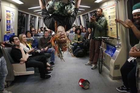 "Member of the Turf Feinz Eric ""eNinga"" Davis, 26, flips head-over-heels during a Turf dance show for an audience on a BART train on Friday Feb. 27, 2015 in San Francisco, Calif."