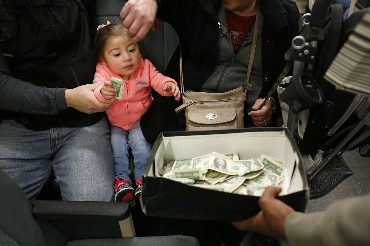Diana Santos, 2, of El Sobrante, puts a dollar in the shoebox after members of the Turf Feinz danced on a BART train on Friday Feb. 27, 2015 in San Francisco, Calif.