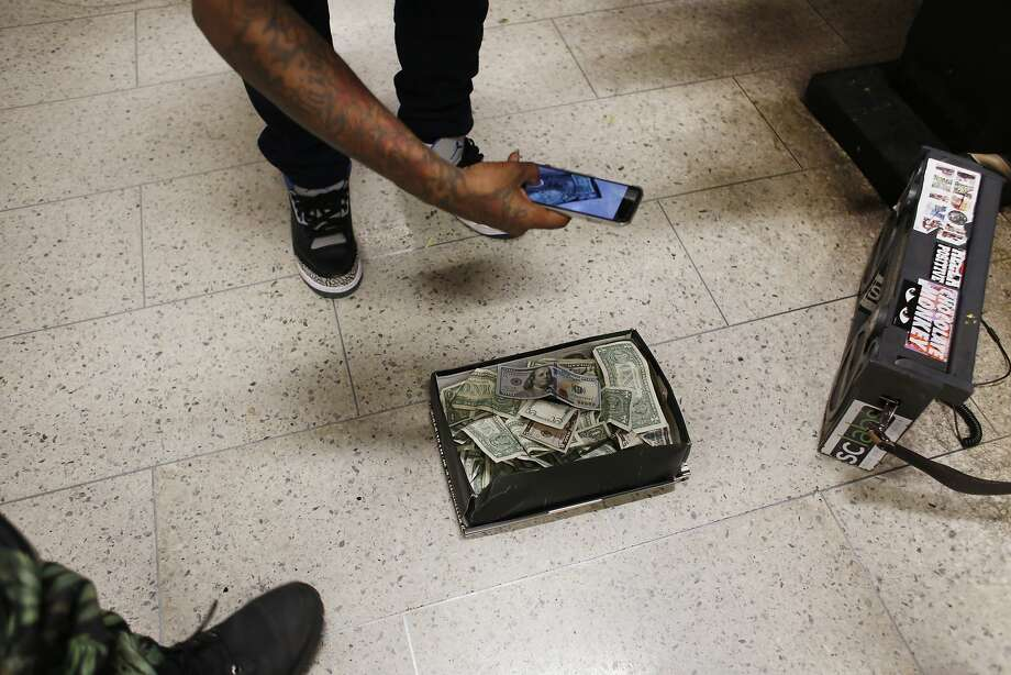 "Member of the Turf Feinz Eric ""eNinga"" Davis snaps a photo of his $100 bill after hours of Turf dance performances on BART. Photo: Mike Kepka, The Chronicle"