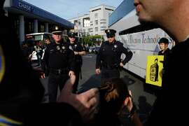 Police officers confront protesters blocking a Facebook bus (left) and Google bus from passing in San Francisco in 2014.