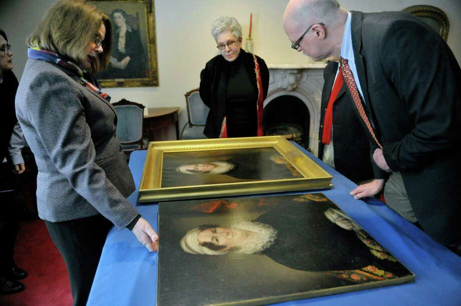 Tammis Groft, left, executive director of the Albany Institute of History and Art, Susan B. Strange, center, from Potomac, Md., and Doug McCombs, right, chief curator at the institute, look over paintings of Betsey Foot at the Albany Academy for Girls on Thursday, March 5, 2015, in Albany, N.Y.  Foot is the great, great, great grandmother of Strange and a niece of Strange brought in the painting of Foot, foreground, to see if the two painting could be matched to the same artist.  Groft and McCombs were on hand to try to figure out if artist Ezra Ames painted them both.     (Paul Buckowski / Times Union) Photo: PAUL BUCKOWSKI / 10030889A