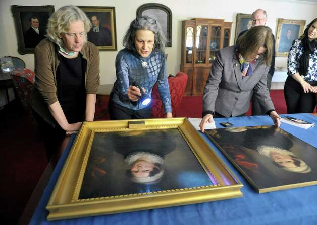 Pam Burr Smith, left, from Brunswick, Maine, Joyce Zucker, center, a painting conservator, and Tammis Groft, right, executive director of the Albany Institute of History and Art, look over paintings of Betsey Foot at the Albany Academy for Girls on Thursday, March 5, 2015, in Albany, N.Y. Foot is the great, great, great, great  grandmother to Smith. Smith brought in the painting of Foot, on the right, to see if the two paintings could be matched to the same artist. (Paul Buckowski / Times Union) Photo: PAUL BUCKOWSKI / 10030889A
