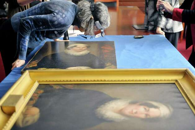 Joyce Zucker, a painting conservator, looks over a painting of Betsey Foot at the Albany Academy for Girls on Thursday, March 5, 2015, in Albany, N.Y.  The painting that Zucker is looking at was brought in by Pam Burr Smith, from Brunswick, Maine. Foot is the great, great, great, great grandmother to Smith. Smith brought in the painting of Foot, to see if the two paintings could be matched to the same artist. (Paul Buckowski / Times Union) Photo: PAUL BUCKOWSKI / 10030889A