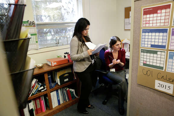 San Mateo County communicable disease investigators Cynthia Amezcua (left) and Carly Bock discuss measles cases in their offices. San Mateo County has had four cases of measles so far this year, with 17 cases reported in the Bay Area.