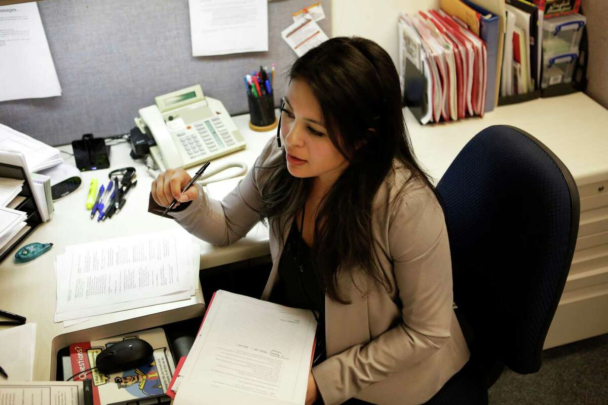 Cynthia Amezcua, a communicable disease investigator, talks with a measles patient from her desk in the San Mateo County Public Health System offices in San Mateo.