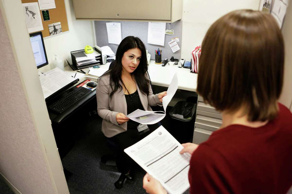 San Mateo County communicable disease investigators Cynthia Amezcua (left) and Carly Bock talk together in their offices in San Mateo, where four caes of measles have been reported.