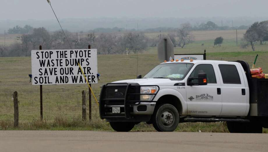 A truck drives by a protest sign posted against the building of the Pyote Reclamation Systems LLC oil and gas solid waste disposal facility near Nordheim in DeWitt County. The facility would accept drill cuttings, drilling fluids and soil contaminated by crude oil. Photo: Billy Calzada /San Antonio Express-News / San Antonio Express-News