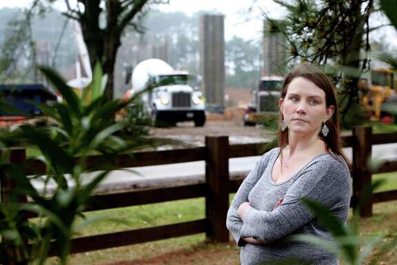 Lindsey Michalak-Kindall stands in front of her home along the 4100 block of Lonesome Pine Road where the Grand Parkway is cutting across northern Harris County Tuesday, March 3, 2015, in Spring, Texas. The toll gantry is being constructed right in front of her house. Kindall desperately wants a sound wall, to which the builders are saying it's too late.