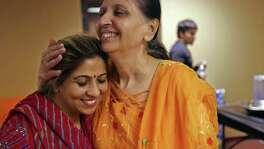 Sangeeta Dua, de India y dueña del Centro de belleza Apsara, es abrazada por su amiga Jyoti Thakkar, presidenta de la junta directiva del templo Jalaram Saibaba, durante la celebración de Sandhya Aarthi.