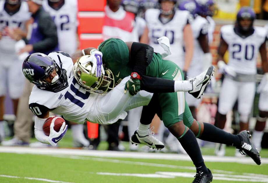 TCU wide receiver Matt Brown is tackled by Baylor linebacker Taylor Young in the first half on Oct. 11, 2014, in Waco. Photo: Rod Aydelotte /Waco Tribune-Herald / Waco Tribune Herald
