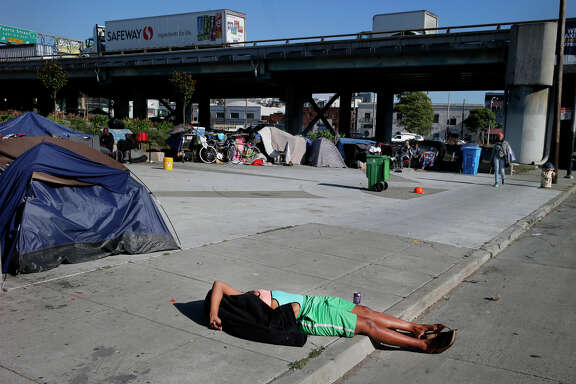 A homeless woman lies passed out on the sidewalk across from a park near the Bay Bridge that's become a homeless camp.