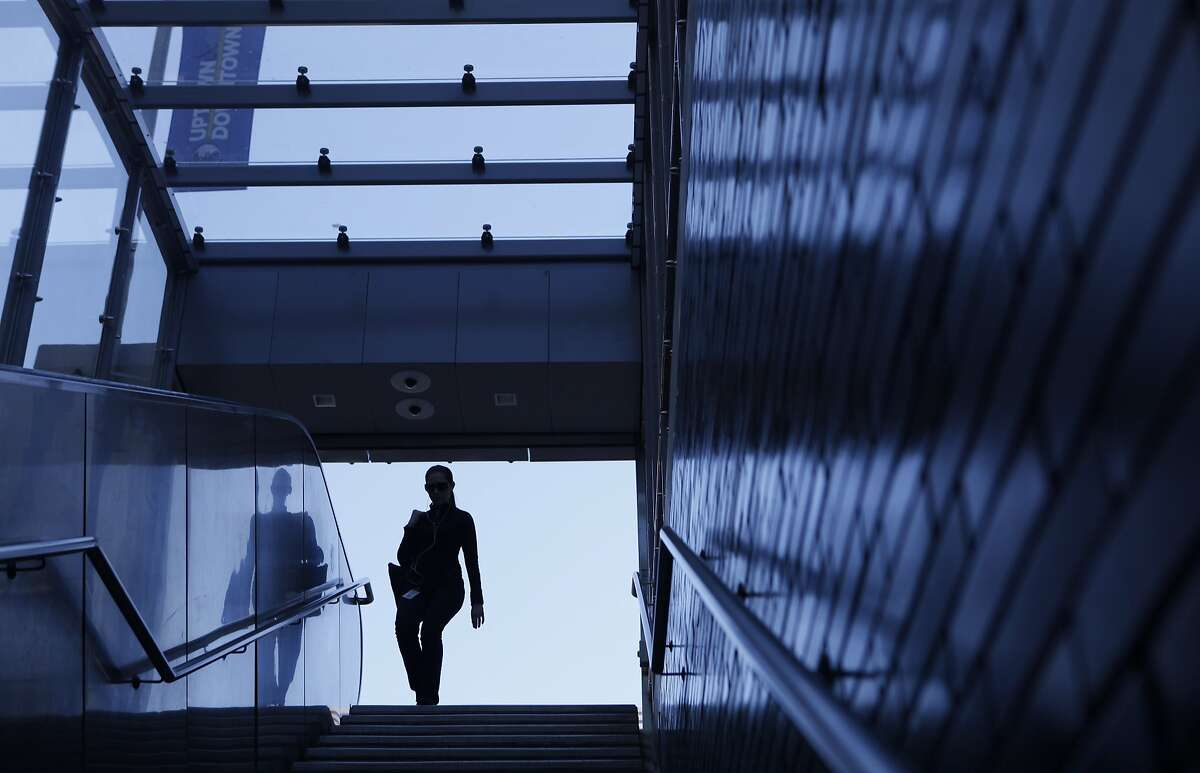 A woman walks down the stairs under the new canopy over the19th Street Bart Station entrance at 20th and Broadway streets in Oakland, Calif. is opened to the public Friday, March 6, 2015.