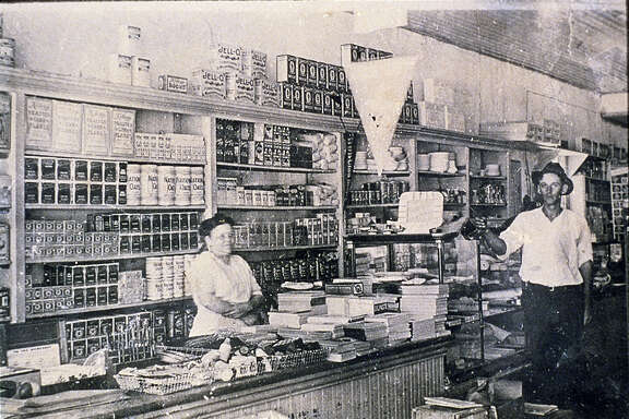 H-E-B founder Florence Butt behind the counter of the first store. Other person not identified. Undated courtesy photo