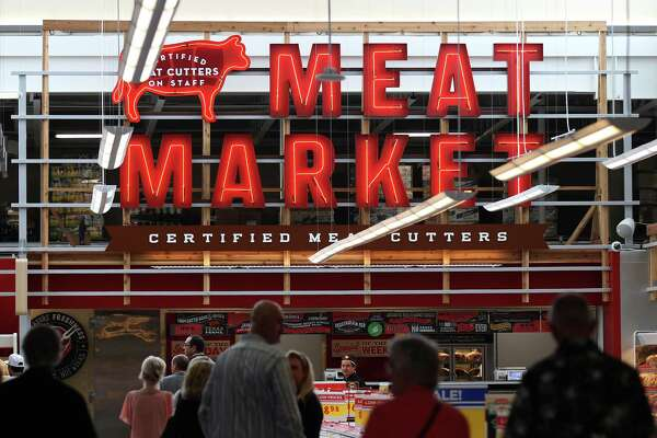Guests walk nearby the meat market section of H-E-B's Market at Stone Oak on June 19, 2014. The new store features an extensive beer and wine section, a charcuterie and a full service restaurant and bar.