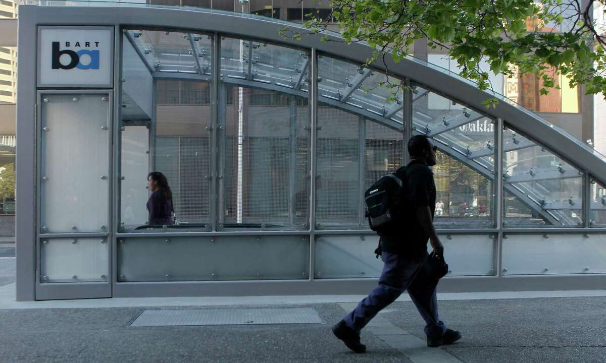 A commuter descends into the 19th Street BART Station in Oakland under the new entrance canopy.