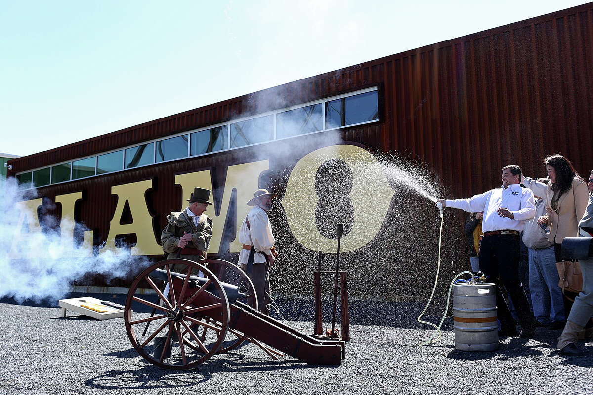 Alamo Beer Co. president Eugene Simor, right, sprays beer from a keg while Gary Luinstra, far left, and William Manuel fire a canon during the Alamo Beer Company Brewery, Beer Hall and Beer Garden Grand Opening on Friday, March 6, 2015.