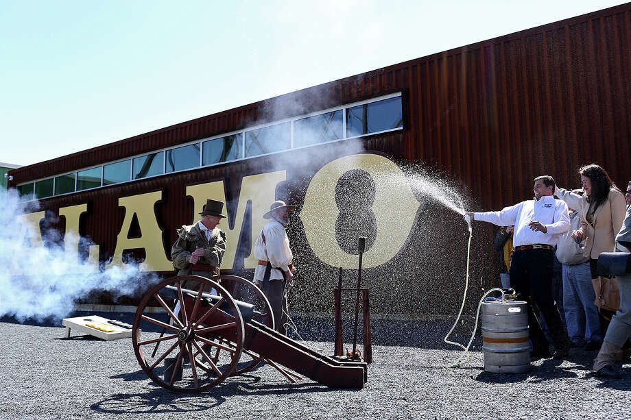 Alamo Beer Co. president Eugene Simor, right, sprays beer from a keg while Gary Luinstra, far left, and William Manuel fire a canon during the Alamo Beer Company Brewery, Beer Hall and Beer Garden Grand Opening on Friday, March 6, 2015. Photo: Lisa Krantz, Staff / San Antonio Express-News / ©2014 San Antonio Express-News