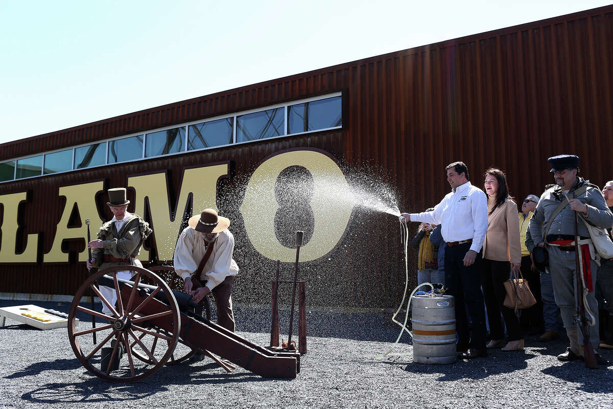 Alamo Beer Co. president Eugene Simor, right, with his wife, Neriza Simor, sprays beer from a keg while Gary Luinstra, far left, and William Manuel work to fire a canon during the Alamo Beer Company Brewery, Beer Hall and Beer Garden Grand Opening on Friday, March 6, 2015.