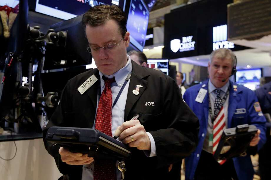 Trader Joseph Murray, left, works on the floor of the New York Stock Exchange, Friday, March 6, 2015. Stocks opened lower on Friday as another strong U.S. jobs report raised the likelihood that the Federal Reserve would start to raise interest rates later this year.  (AP Photo/Richard Drew) ORG XMIT: NYRD105 Photo: Richard Drew / AP