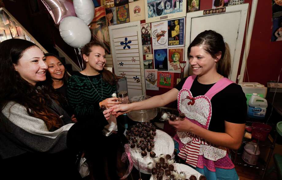 Owner Sarah Rhoades, right,  is all smiles as she hands out cake pops at the opening of her new business Sprinkleista Friday morning March 6, 2015 at 154 Jay Street in Schenectady, N.Y.  (Skip Dickstein/Times Union) Photo: SKIP DICKSTEIN / 10030867A