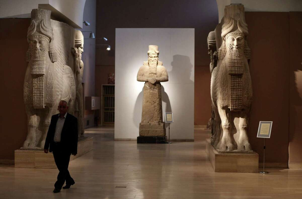 FILE - In this March 1, 2015. file photo, a man at Iraq's National Museum in Baghdad walks past two ancient Assyrian human-headed winged bull statues. Islamic State militants