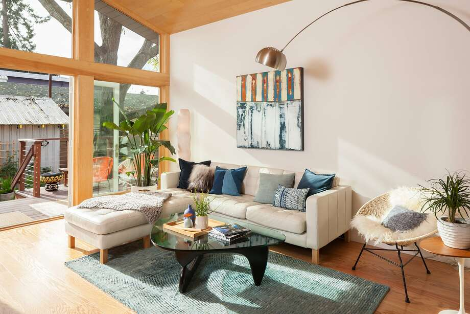 Brightly colored accent pieces provide warmth to this industrialized great room in Oakland. Photo: Photography By Peter Lyons Photo