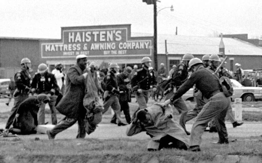 In this March 7, 1965 photo, state troopers club participants of a civil rights voting march in Selma, Ala. At right, John Lewis, chairman of the Student Nonviolent Coordinating Committee, is beaten by a state trooper.  Photo: STR / AP