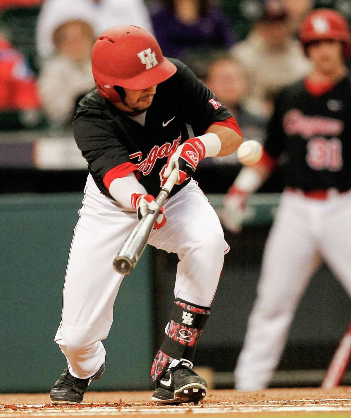 Houston infielder Josh Vidales (8) lays down a bunt against the LSU Tigers during the College Classic on March 6, 2015 at Minute Maid Park in Houston, Texas.