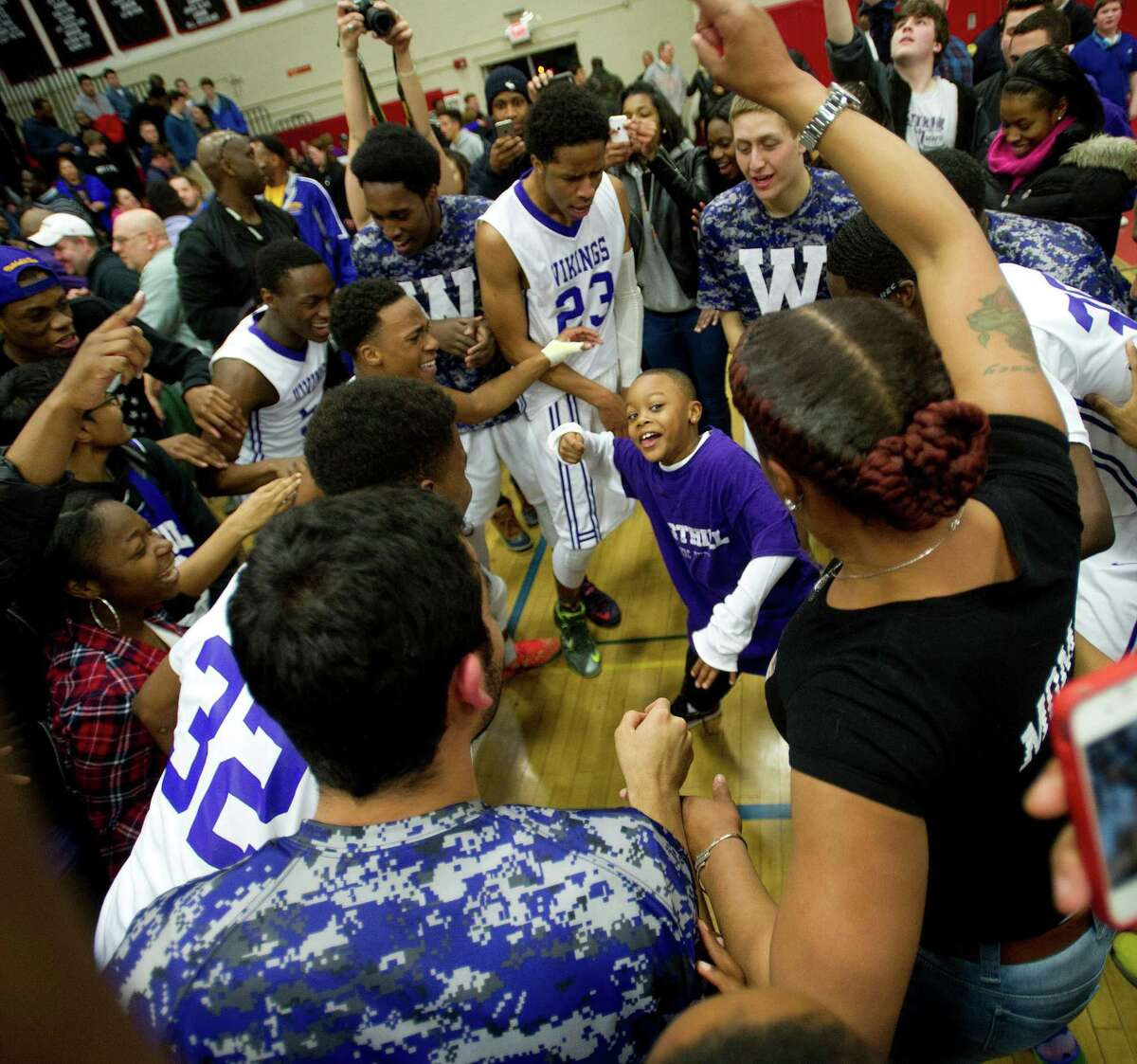 Westhill players surround Raheem Hargrove-Murray, 7, as they dance to celebrate winning Friday's FCIAC Boys Basketball Championship game between Westhill and Norwalk High Schools at Fairfield Warde High School in Fairfield, Conn., on Friday, March 6, 2015.