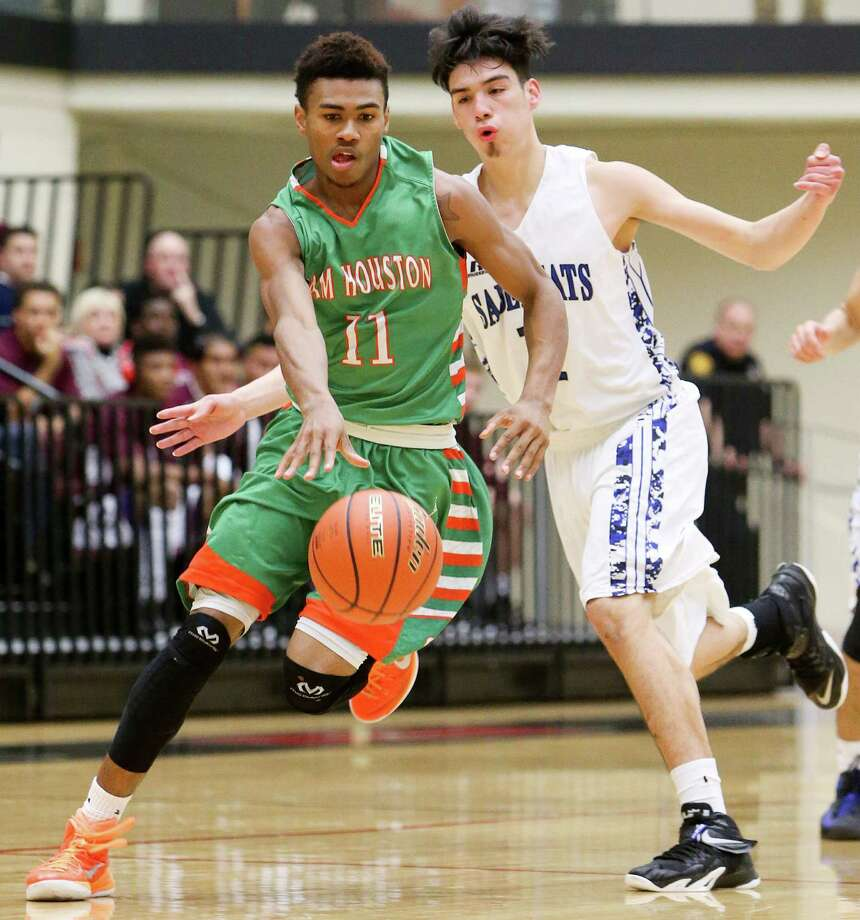 Sam Houston's Juwan Anderson (left) brings the ball upcourt past Edinburg Vela's Mark Castillo during the first half of their Region IV-5A semifinal game at Littleton Gym on Friday, March 6, 2015. Sam Houston earned a trip to the finals with a 66-58 victory over the SaberCats.  MARVIN PFEIFFER/ mpfeiffer@express-news.net Photo: Marvin Pfeiffer, Staff / San Antonio Express-News / Express-News 2015