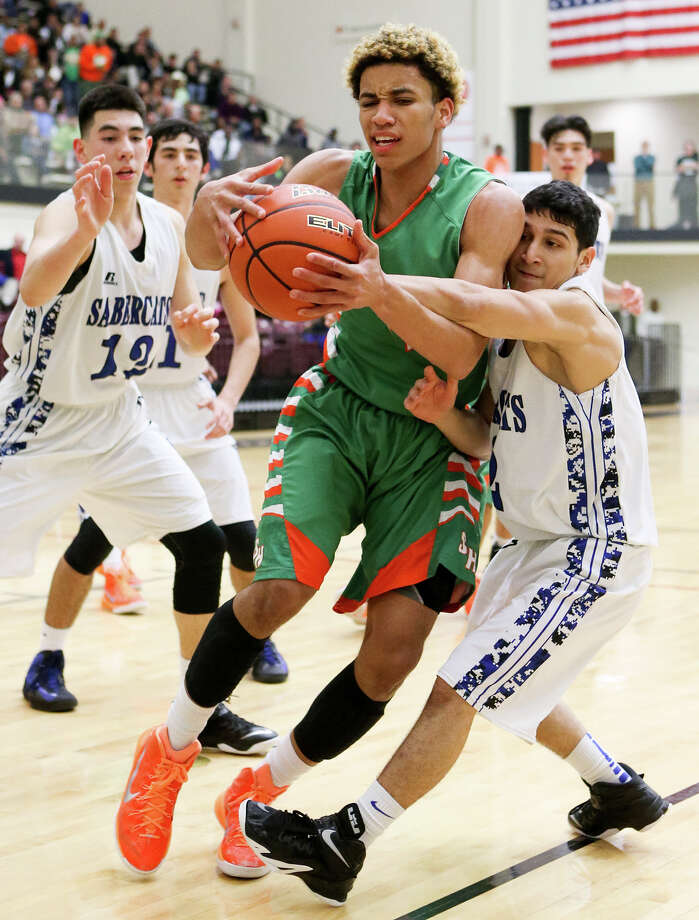 Sam Houston's Robert Christian (center) fights for possession of the ball with Edinburg Vela's Christian Enriquez during the second half of their Region IV-5A semifinal game at Littleton Gym on March 6, 2015. Photo: Marvin Pfeiffer /San Antonio Express-News / Express-News 2015