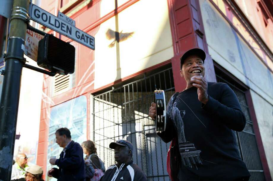 "Rob Robinson, right, a member of the choir at Saint Boniface Catholic Church, sings gospel music with others on the corner of Golden Gate Ave and Jones St. as part of the ""4 Corner Fridays"" event in the Tenderloin March 6, 2015 in San Francisco, Calif. Friday was the third in the new monthly ""4 Corner Fridays"" event in which local groups come out with music, popcorn, free books, games and information on their services to try to create a positive, fun atmosphere in areas that struggle with drug dealing and other issues. Photo: Leah Millis / The Chronicle / ONLINE_YES"