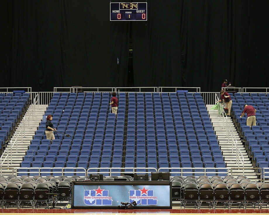 Workers clean up the seating area between sessions 5 and 6 of the UIL Girls Basketball State Championships semifinals at the Alamodome, Friday, March 6, 2015. This is the first time the event is in San Antonio, and the first time in more than 90 years it's not being held in Austin. Photo: JERRY LARA, Staff / San Antonio Express-News / © 2015 San Antonio Express-News