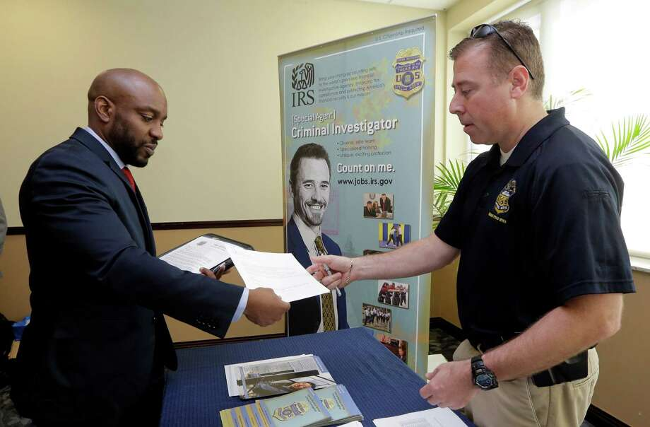 In this Feb. 6, 2015 photo, U.S. Marine Corps Veteran Arlington Robertson, of Fort Lauderdale, left, hands his resume to an Internal Revenue Service Special Agent, at the annual Veterans Career and Resource Fair in Miami. Photo: Alan Diaz, STF / AP