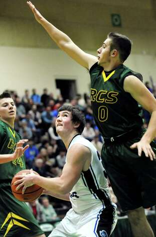 Hoosick Falls' Mark Hackett, center, looks to the hoop as Ravena's Matt Ferriero defends during their Class B boys basketball semifinals on Friday, March 6, 2015, at Hudson Valley Community College in Troy, N.Y. (Cindy Schultz / Times Union) Photo: Cindy Schultz / 10030880A
