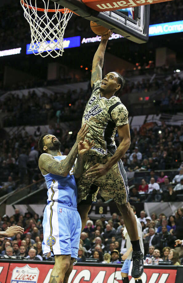 Kawhi Leonard goes up to try a slam against Wilson Chandler in the second half as the Spurs play the Denver Nuggets at the AT&T Center on March 6, 2015. Photo: Tom Reel, San Antonio Express-News