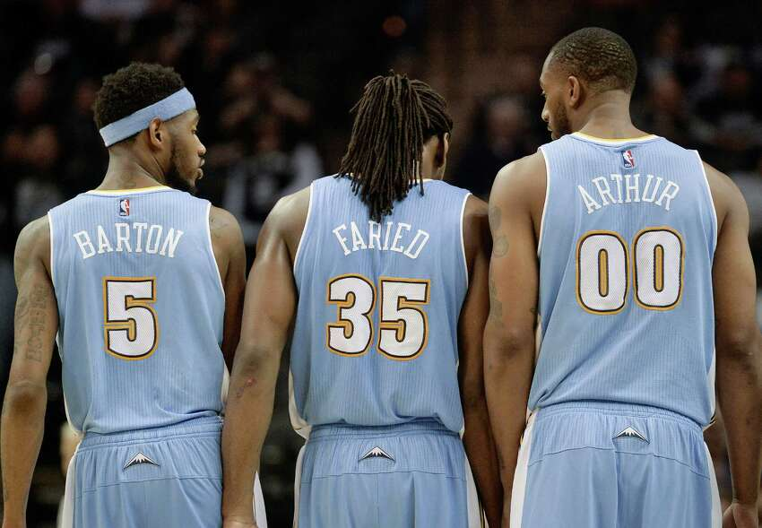 Denver Nuggets forward Kenneth Faried, center, walks with teammates Will Barton, left, and Darrell Arthur, during the second half of an NBA basketball game against the San Antonio Spurs, Friday, March 6, 2015, in San Antonio. San Antonio won 120-111. (AP Photo/Darren Abate)