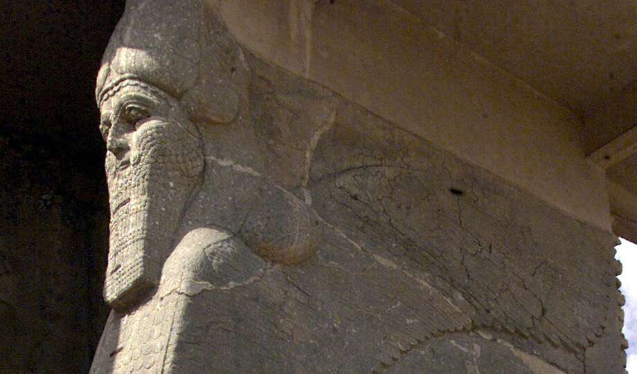 An Iraqi worker stands 21 April 2001 next to the ancient statue of a winged bull with a human face, an indication of strength in the Assyrian civilization, at the archaeological site of Nimrud, south of Mosul in northern Iraq. Nimrud was built in the 13th century B.C. during Mesopotamia's Assyrian era and excavations, carried on since the mid-19th century, have revealed remarkable finds. AFP PHOTO/Karim SAHIBKARIM SAHIB/AFP/Getty Images Photo: KARIM SAHIB, Staff / AFP / Getty Images / AFP