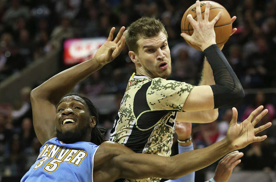 Tiago Splitter rips the ball away from Kenneth Faried as the Spurs play the Denver Nuggets at the AT&T Center on March 6, 2015. Photo: Tom Reel /San Antonio Express-News