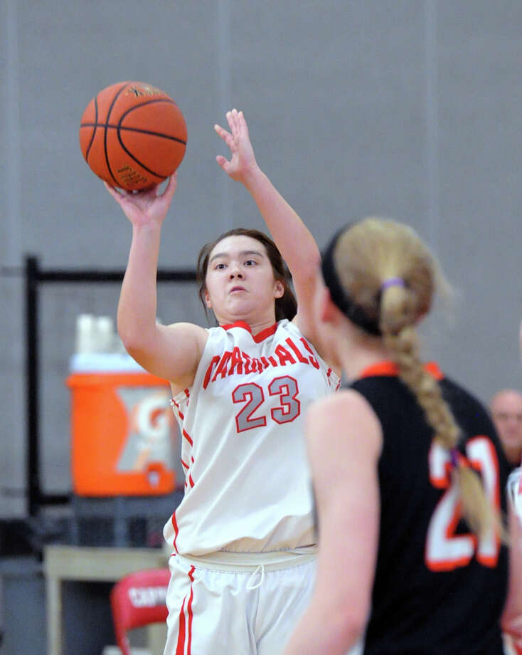 At left, Jamie Kockenmeister (#23) of Greenwich connects on a three-point shot over Ridgefield's Rebecca Lawrence (#21), right, during the girls state high school basketball playoff game between Greenwich High School and Ridgefield High School at Greenwich, Conn., Saturday, March 7, 2015. Photo: Bob Luckey / Greenwich Time