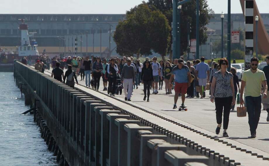 Crowds walk along the Embarcadero and enjoy the warm weather in San Francisco on March 7. Photo: Jessica Christian / The Chronicle / ONLINE_YES