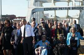 President Obama (white shirt), first lady Michelle Obama (left) and U.S. Rep. John Lewis (between them), D-Ga., lead a walk across the Edmund Pettus Bridge to mark 50 years since the Selma to Montgomery civil rights marches in Alabama.