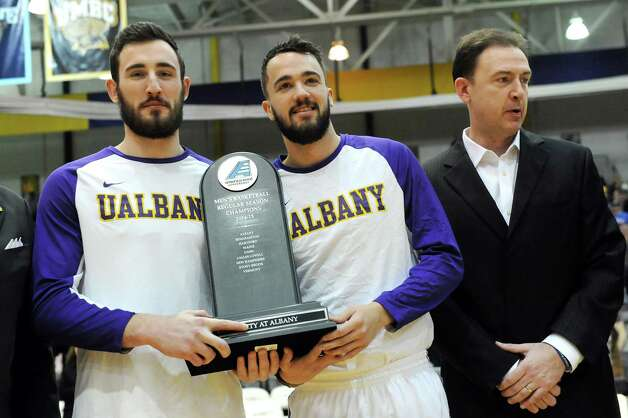 UAlbany's Sam Rowley, left, and Peter Hooley, center, hold the regular season championship trophy before their basketball game against Vermont on Saturday, Feb. 28, 2015, at UAlbany in Albany, N.Y. At right is coach Will Brown. (Cindy Schultz / Times Union) Photo: Cindy Schultz / 00030743A