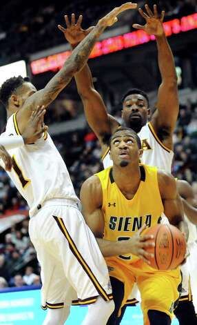 Siena's Jimmy Paige, center, looks to shoot as Iona's Isaiah Williams, left, and Kelvin Amayo defend during their quarterfinal game of the MAAC Championship on Saturday, March 7, 2015, at Times Union Center in Albany, N.Y. (Cindy Schultz / Times Union) Photo: Cindy Schultz / 00030912A