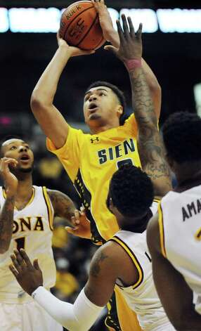 Siena's Javion Oguyemi, center, goes to the hoop during their quarterfinal game against Iona in the MAAC Championship on Saturday, March 7, 2015, at Times Union Center in Albany, N.Y. (Cindy Schultz / Times Union) Photo: Cindy Schultz / 00030912A