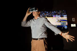 Warriors co-owner Peter Guber watches his team through the NextVR virtual reality glasses, which can put fans right next to the action, even if they don't have a prime seat like Weston Stankowski of San Francisco, below.