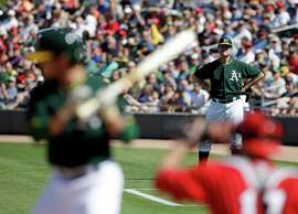 Michigan football coach Jim Harbaugh watches from the first bast coaches box during the third inning of a spring training baseball game between the Los Angeles Angels and Oakland Athletics Saturday, March 7, 2015, in Mesa, Ariz. (AP Photo/Darron Cummings)
