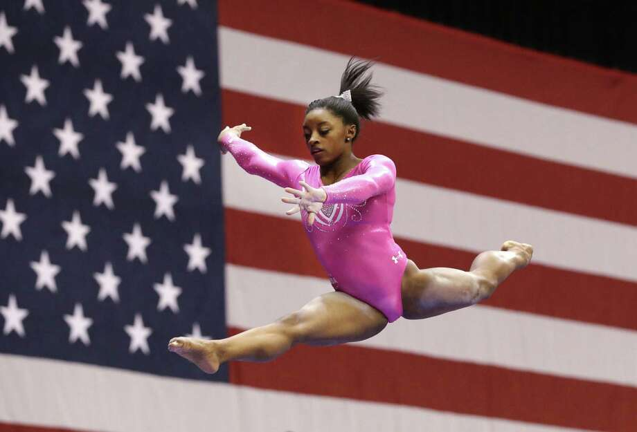 Simone Biles jumps off the balance beam during the American Cup gymnastics competition Saturday, March 7, 2015, in Arlington, Texas. Biles led from the start in a record-setting winat the American Cup in her first competition since taking a second straight world all-around title last year. (AP Photo/LM Otero) Photo: LM Otero, Associated Press / AP